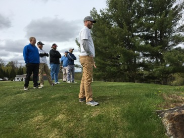 Watching the first group tee-off.